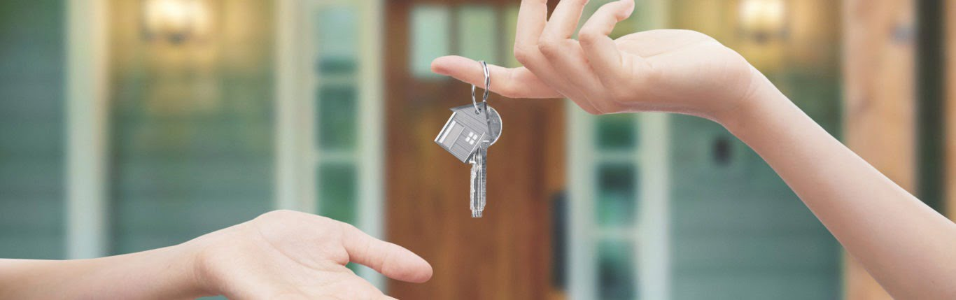 landlord hand giving keys to hand of renter
