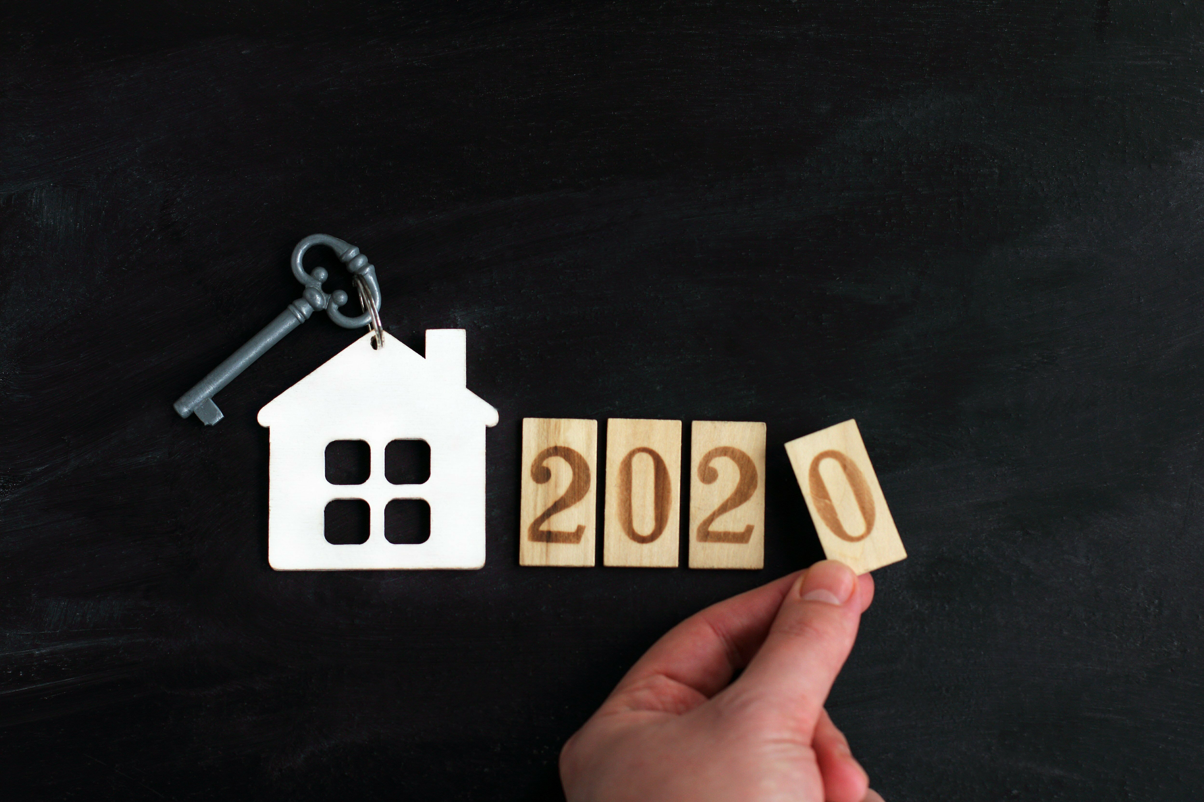 model of a house with a key next to the number 2020 and a hand. build individual housing in the new year