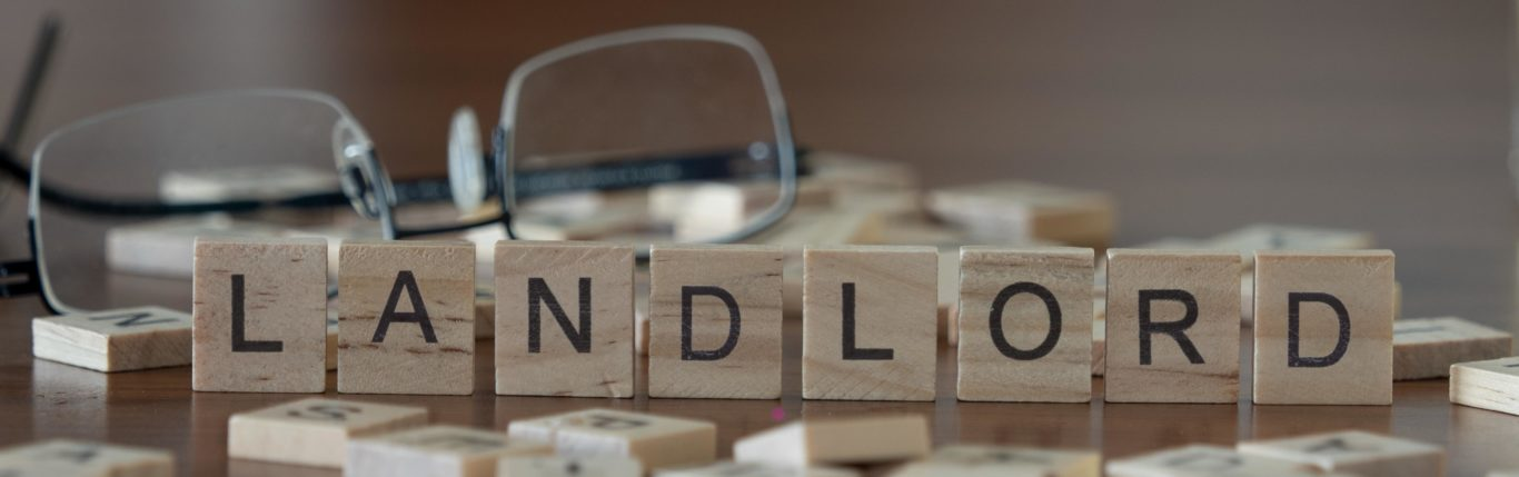 """Glasses And Some Wooden Block On The Table Showing Word """"Landlord"""" - Bancroft & Associates"""