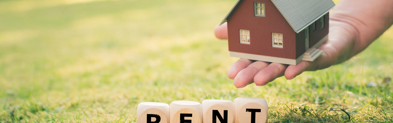 """A Tiny House And Some Wooden Block On The Grass Showing Word """"Rent"""" - Bancroft & Associates"""