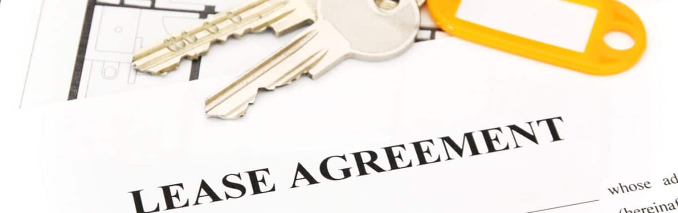 A Lease Agreement, A Pen And Two Keys With Keychain - Bancroft & Associates